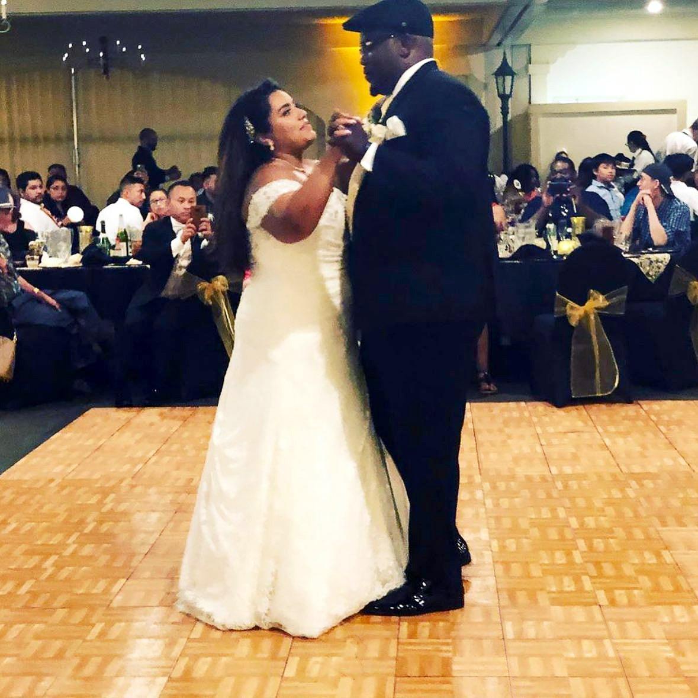 Couple dances at wedding on an Oak style dance floor